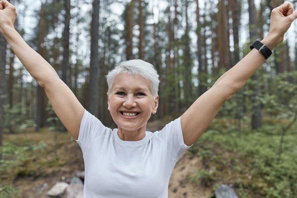 Energifyldt kvinde med armene i vejret